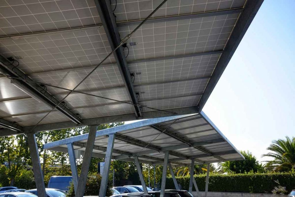 Estacionamiento con paneles solares visto desde abajo, con vista del panel solar y la estructura