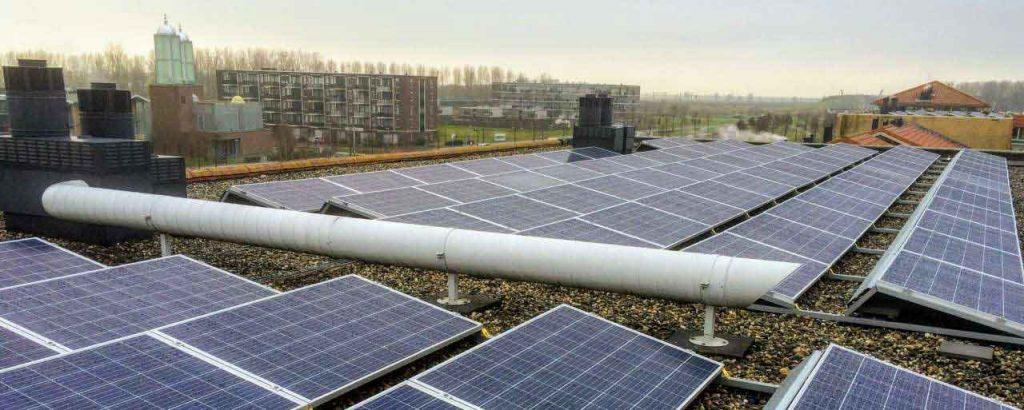 Nave industrial con paneles solares, la ciudad se ve de fondo