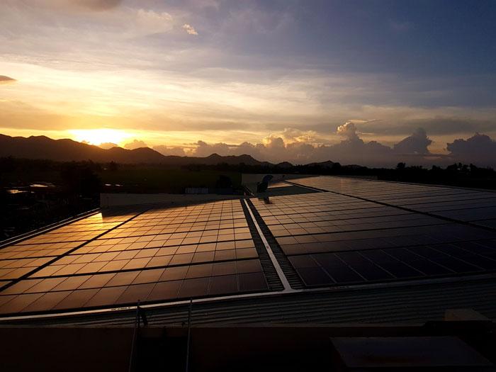 hermoso atardecer, sobre un techo industrial lleno de miles de paneles solares